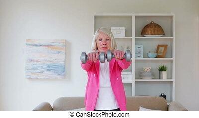 Senior woman using dumbbells at home