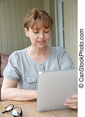 Senior woman using electronic tablet at home