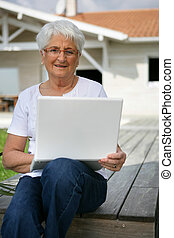 Senior woman using her laptop outdoors
