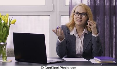 Senior woman using laptop and cellphone at work