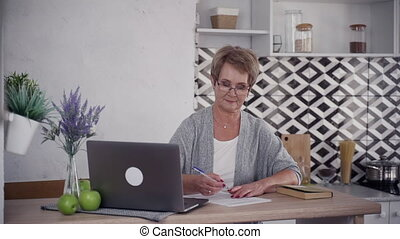 Senior woman using laptop at home and making notes -...