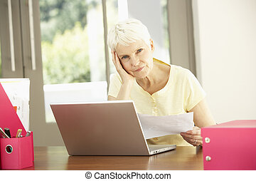 Senior Woman Using Laptop At Home