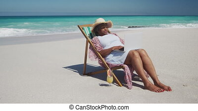 Senior woman using laptop at the beach
