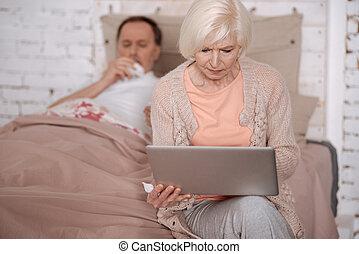 Senior woman using laptop near her ill husband