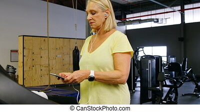 Senior woman using mobile phone during exercise 4k - Senior...