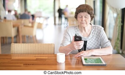 Senior Woman Using Phone While Thinking At The Coffee Shop -...