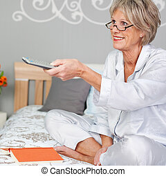 Senior Woman Using Remote Control To Changing Channels In Bed