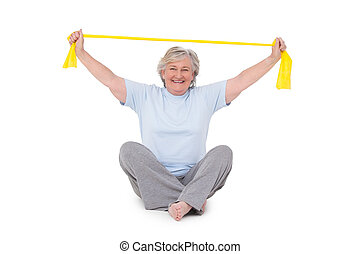 Senior woman using resistance band on white background