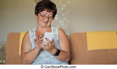 Senior Woman Using Smart Phone At Home