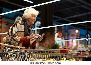 Senior Woman Using Smartphone in Supermarket