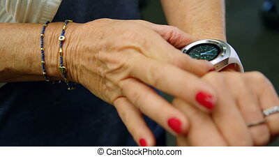 Senior woman using smartwatch in fitness studio 4k -...