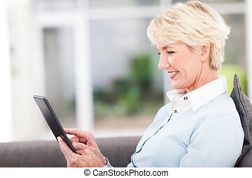 senior woman using tablet computer - pretty senior woman...