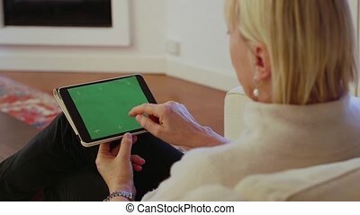 senior woman using touch pad device - portrait of beautiful...