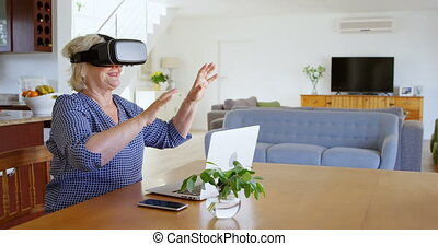 Senior woman using virtual reality headset at home 4k