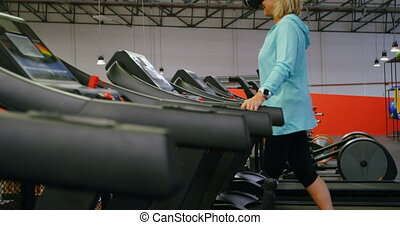 Senior woman using virtual reality headset on treadmill 4k