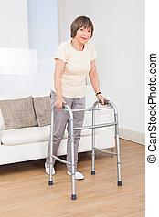 Senior Woman Using Walking Frame - Full length portrait of...