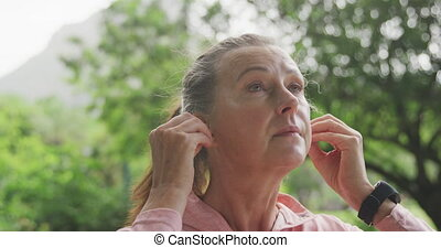 Senior woman using wireless earphones in the park - Senior ...
