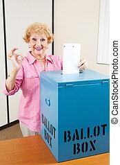 Senior Woman Voting AOkay - Senior woman drops her ballot in...