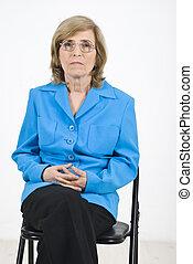 Senior woman waiting on chair