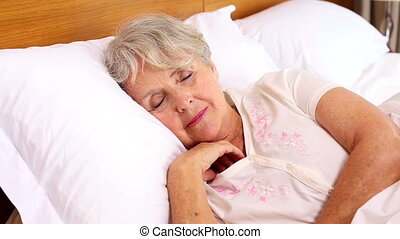 Senior woman waking up in her bed