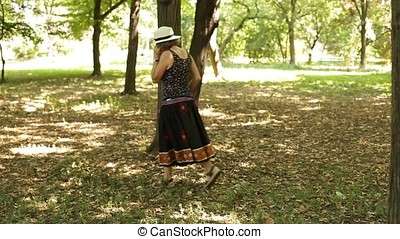 Senior Woman Walking and Talking on Mobile Phone in Forest