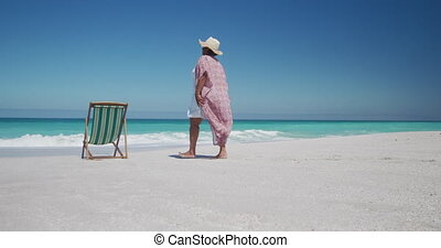 Senior woman walking at the beach