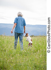 Senior Woman Walking in a Field with her Dog
