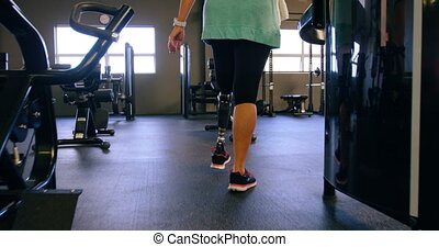 Senior woman walking in fitness studio 4k - Rear view of...