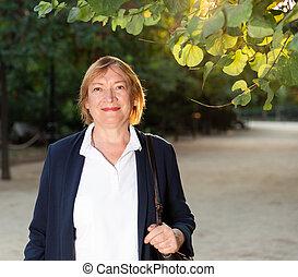 Senior woman walking in green park