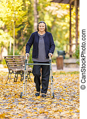 Senior woman walking outdoors with walker in autumn park