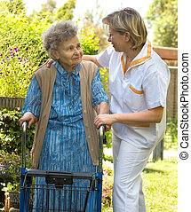 Senior  woman walking with the help of her nurse
