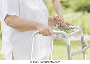 Senior woman walking with the walking frame in the garden