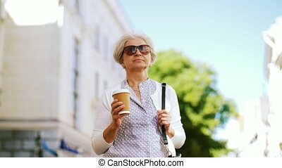 senior woman walks along city and drinks coffee - old age,...