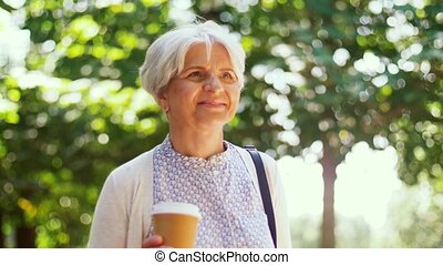 senior woman walks along park and drinks coffee - old age,...