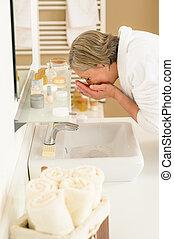 Senior woman wash face at basin bathroom - Senior woman in ...