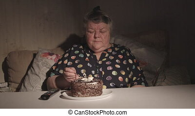 Senior woman watching television and eating cake in a dark room