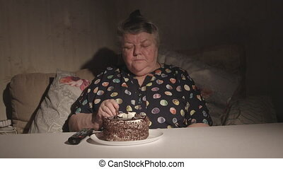 Senior woman watching television and eating cake in a dark room timelapse