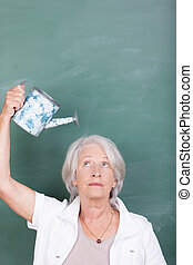 Senior woman watering her head with a small metal watering...