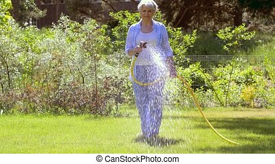 senior woman watering lawn by hose at garden - gardening and...