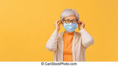 Senior woman wearing facemask during coronavirus and flu ...