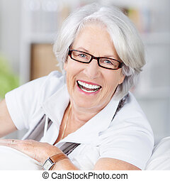 Closeup portrait of happy senior woman wearing glasses at home