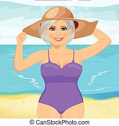 senior woman wearing pink swimsuit and big straw hat at the beach