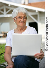 Senior woman with a laptop in the garden