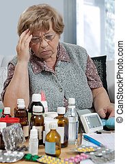 medicine - senior woman with a row of many medicine bottles