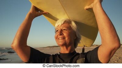 Senior woman with a surfboard smiling