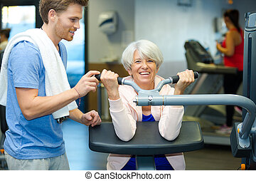 senior woman with an attractive young male trainer