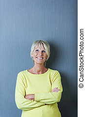 Senior Woman With Arms Crossed Looking Up Against Blue Wall