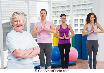 Senior woman with arms crossed standing in gym