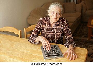 Senior woman with big calculator - Senior woman calculating