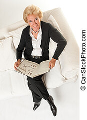 Senior woman with book on a sofa